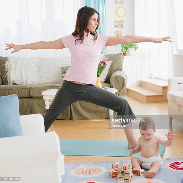 Mother doing yoga, while baby plays
