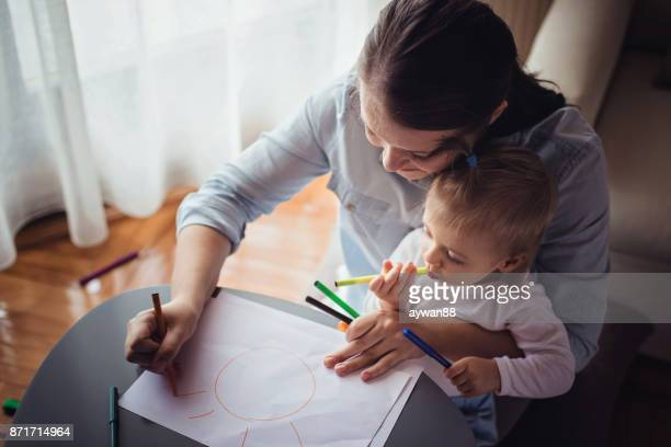 Mother drawing with her cute baby boy