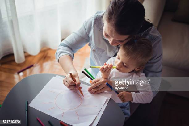 Mother drawing with her cute baby