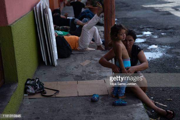 A mother dresses her daughter outside the Mexican Commission for Refugee Assistance on June 21 2019 in Tapachula Mexico Hundreds of people queue up...