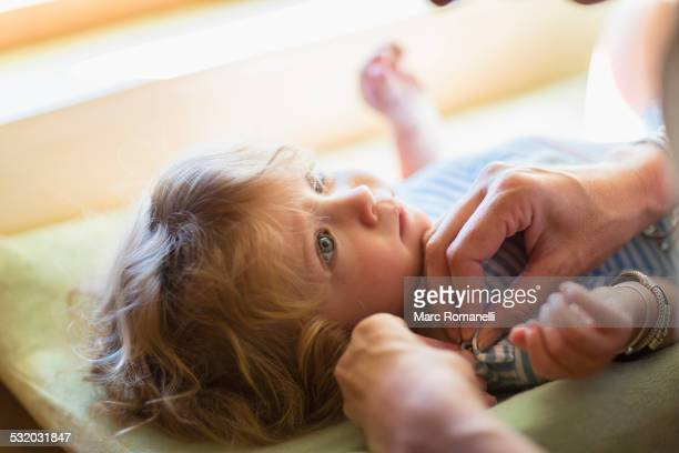Mother dressing baby boy on changing table
