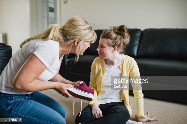 mother dressing disabled daughter at home - learning disability stock pictures, royalty-free photos & images