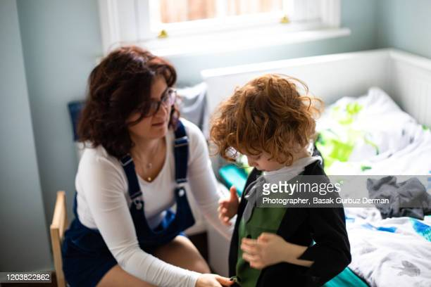 mother dressing her kid in bedroom - child in bed clothed stock pictures, royalty-free photos & images
