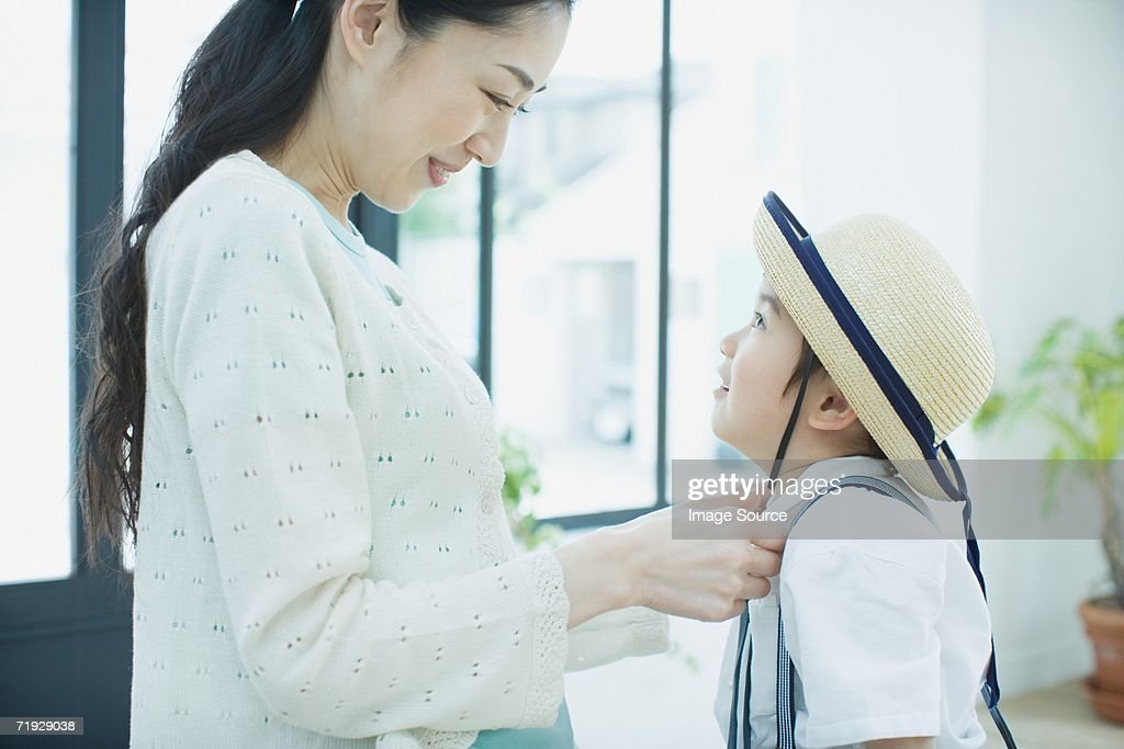 Mother dressing son for school : Stock Photo
