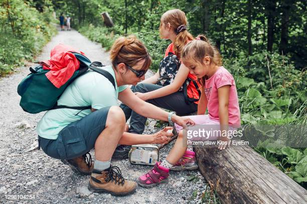 mother dressing the wound on her little daughter's knee with medicine in spray. accident during trip - kids first aid kit stock pictures, royalty-free photos & images