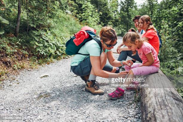 mother dressing the wound on her little daughter's knee with medicine in spray - kids first aid kit stock pictures, royalty-free photos & images