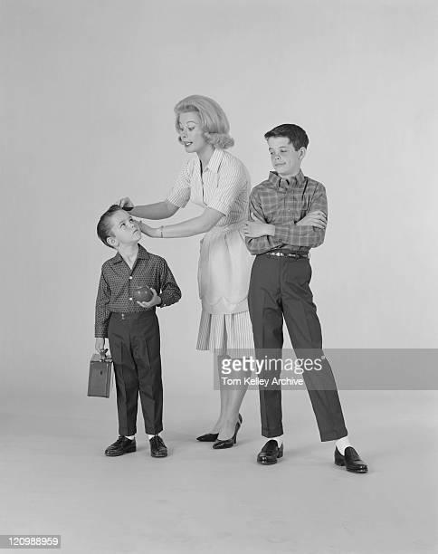 mãe vestindo dois filhos em fundo branco - de arquivo imagens e fotografias de stock