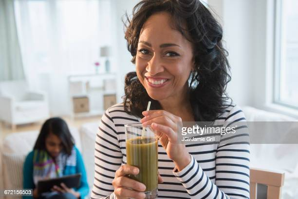 Mother drinking green smoothie while daughter uses digital tablet