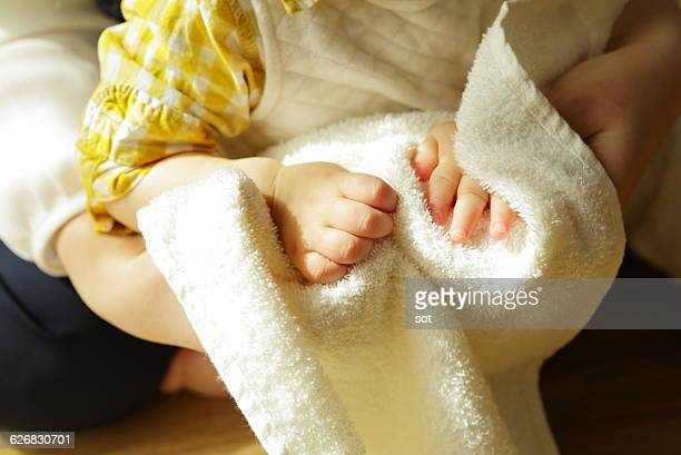 Mother drying hands of baby boy with towel