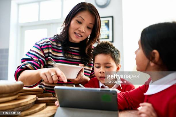 mother eating cereal looking at tablet with two children - one parent stock pictures, royalty-free photos & images