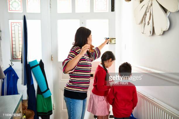 mother eating toast and opening front door for two school children - morning stock pictures, royalty-free photos & images