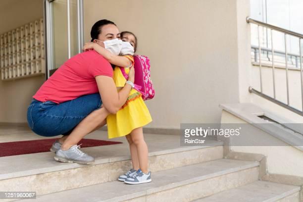 mãe abraça a filha no primeiro dia de aula - criança de escola fundamental - fotografias e filmes do acervo