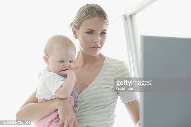 mother embracing baby girl (9-12 months), using laptop at home - 12 23 months stock pictures, royalty-free photos & images
