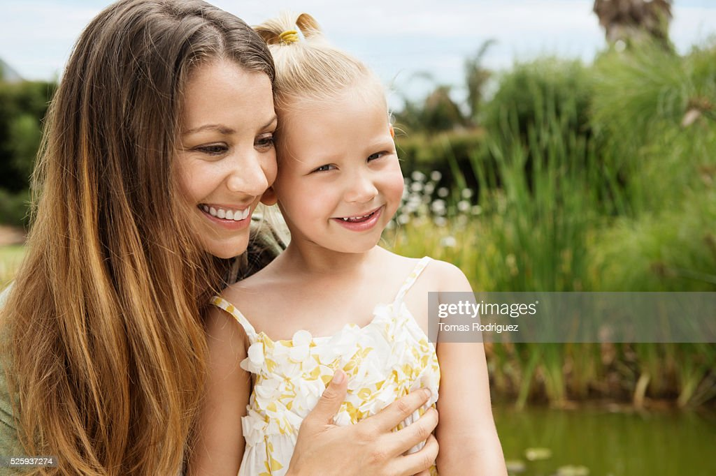 Mother embracing daughter (4-5) outdoors : Stockfoto