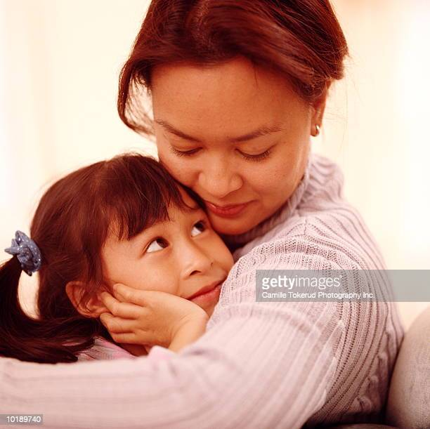 mother embracing daughter (7 years) - 30 39 years imagens e fotografias de stock