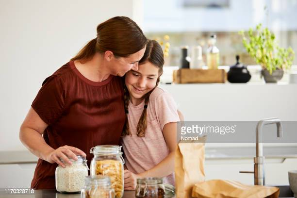 mother embracing girl after unpacking groceries - danish food stock pictures, royalty-free photos & images