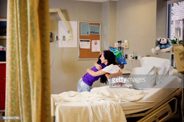 Mother embracing girl while sitting on bed in hospital