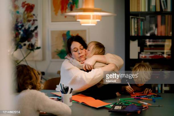 mother embracing girl with down syndrome while sitting by dining table at home - kissing stock pictures, royalty-free photos & images