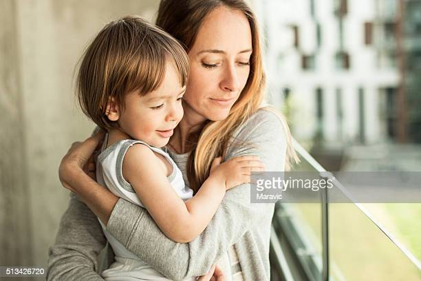 mother embracing her boy - protection stock pictures, royalty-free photos & images