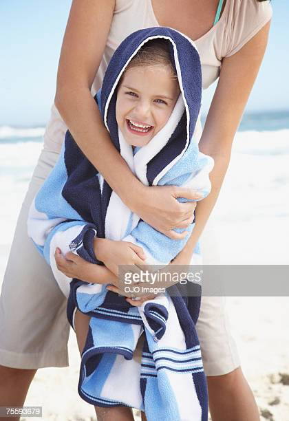 A mother embracing her daughter and wrapping her in a beach towel