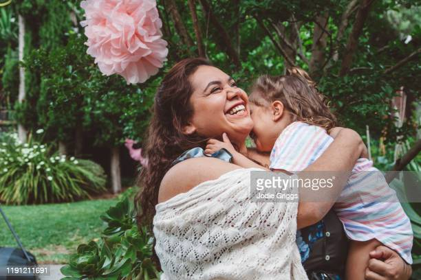 mother embracing her daughter during a family celebration in the backyard - respect stock pictures, royalty-free photos & images