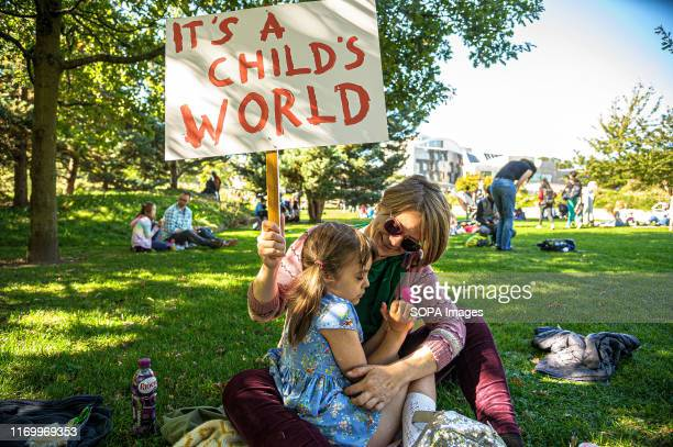 Mother embracing her daughter holds a placard that says its a child's world during the protest. Thousands of parents and students took part in the...