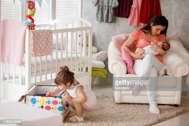 mother embracing her newborn baby girl while her other toddler daughter is playing with toys - 2 5 mesi foto e immagini stock