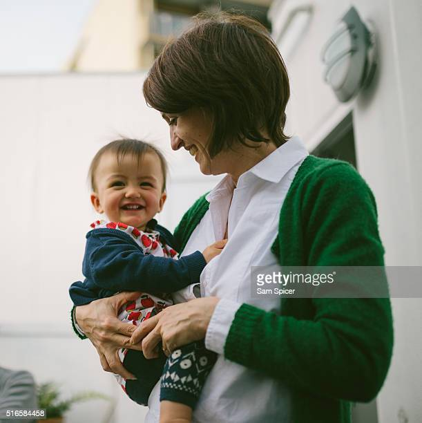 Mother embracing smiling baby daughter