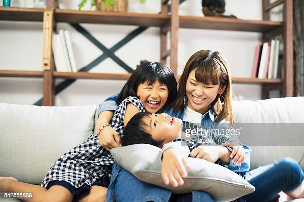 Mother embracing son and daughter on sofa.