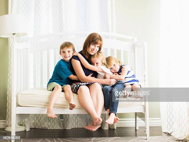 Mother embracing son (8-9) and daughters (4-5, 6-7), Los Angeles, California, USA