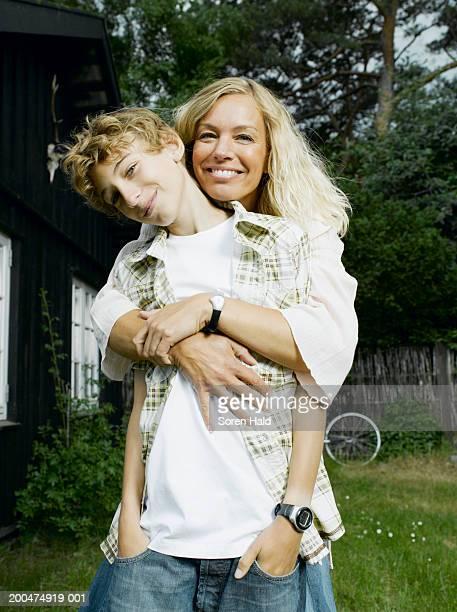 mother embracing son (10-12) in garden, smiling, portrait - 10 11 anni foto e immagini stock