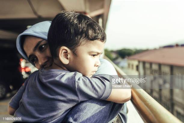 mother embracing todler side view - religious dress stock photos and pictures