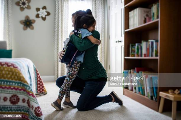mother embracing young daughter before school - education stock pictures, royalty-free photos & images