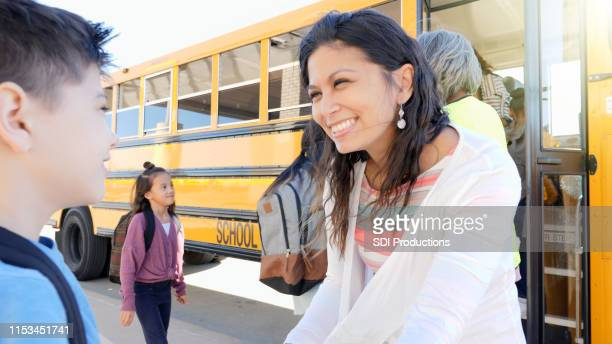 mother encourages son on first day of school - parental leave stock pictures, royalty-free photos & images