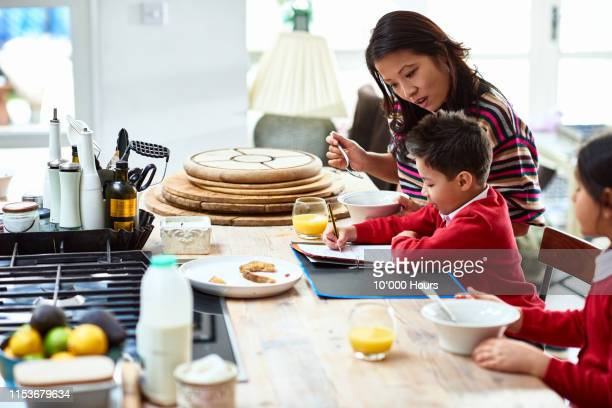 mother encouraging son to do homework at breakfast - east asian ethnicity stock pictures, royalty-free photos & images