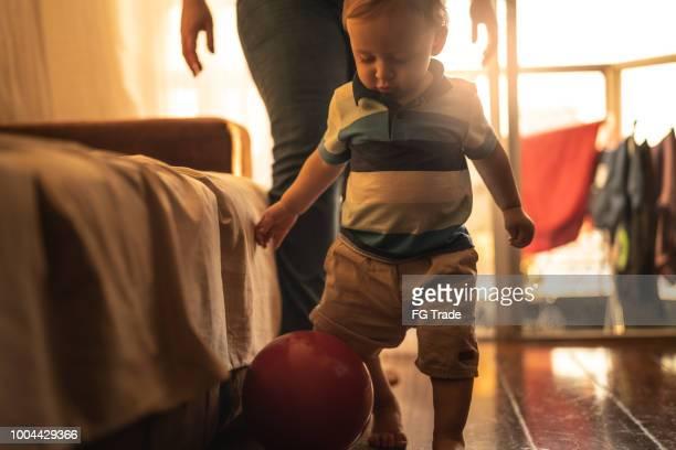 alentar los primeros pasos de un lindo bebé en la casa de la madre - mama futbol fotografías e imágenes de stock