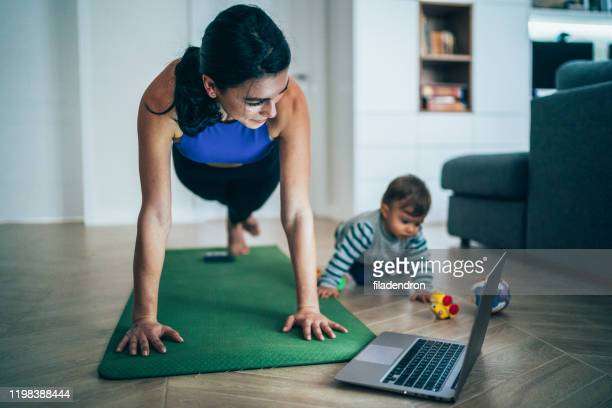 madre esercizio con il suo bambino a casa - esercizio fisico foto e immagini stock