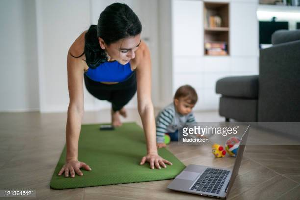 mother exercise with her baby at home - muscular build stock pictures, royalty-free photos & images