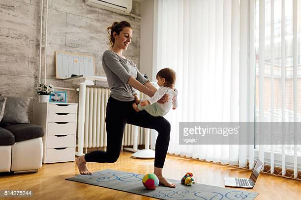"""mother exercise with her baby at home - leanincollection """"working mom"""" stock pictures, royalty-free photos & images"""
