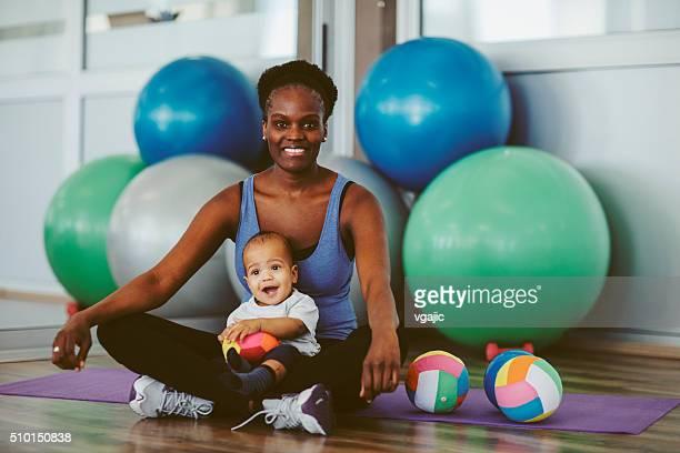 Mère avec son bébé exercices dans une salle de sport.