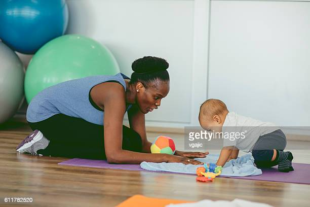 Mother Exercise With Her Baby In a Gym.