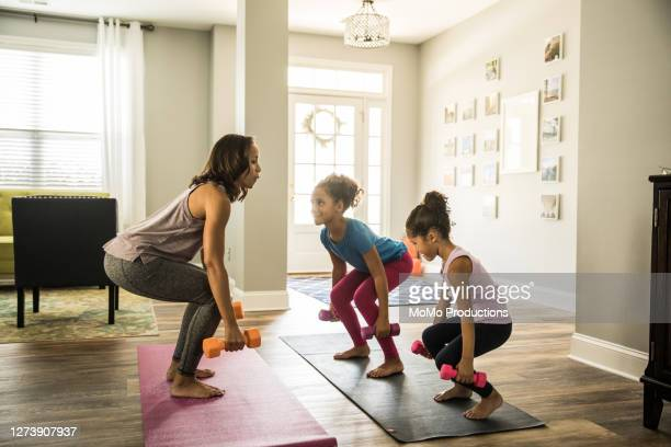 mother exercising at home with young daughters - レギンス ストックフォトと画像