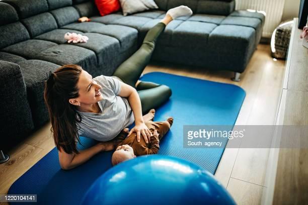 mutter trainiert vor dem fernseher, während ihr kleiner sohn neben ihr liegt - turner syndrome stock-fotos und bilder