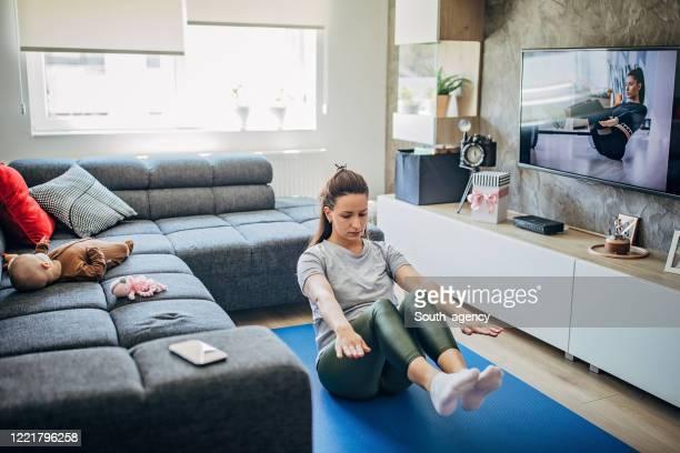 mutter trainiert vor dem fernseher, während ihr kleiner sohn auf dem sofa liegt - turner syndrome stock-fotos und bilder
