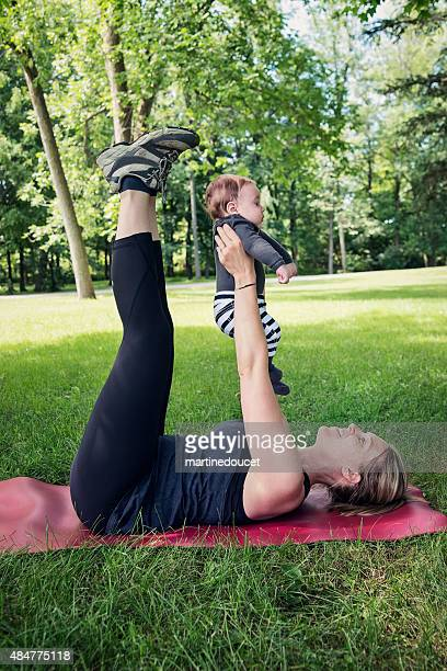 "mother exercising with baby in park in summer. - ""martine doucet"" or martinedoucet stock pictures, royalty-free photos & images"