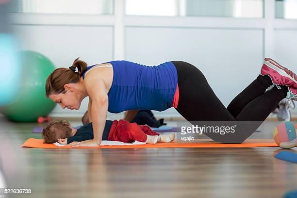 Mère avec son bébé exercices dans une salle de sport