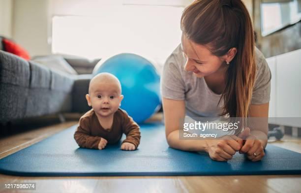mutter trainiert mit ihrem kleinen sohn zu hause - turner syndrome stock-fotos und bilder