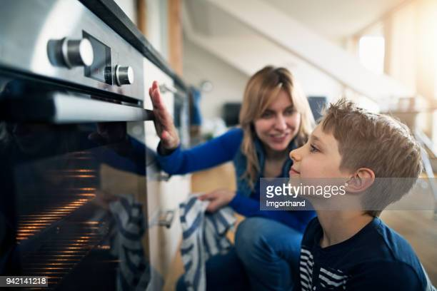 mother explaining oven to her son - hot mom stock photos and pictures