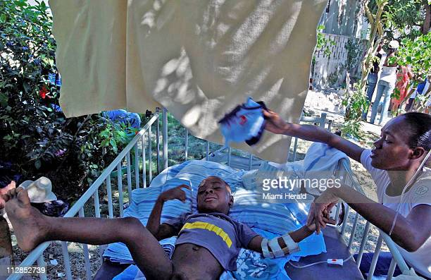 A mother fans her child who received medical attention on Friday January 15 in Jacmel Haiti Relief groups and governments struggled Friday to speed...