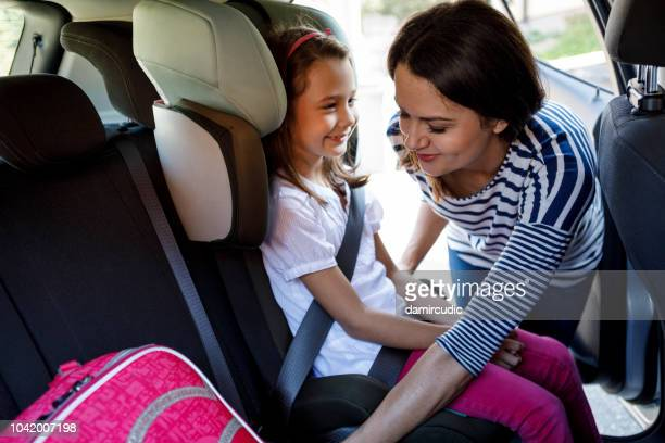 mother fastening child safety seat belt in car - family inside car stock photos and pictures
